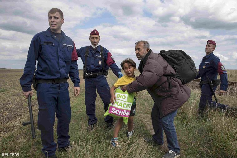 Người cha từng bị László Petra ngáng khi đang bế con trên tay - Ảnh: Marko Djurica (Reuters)