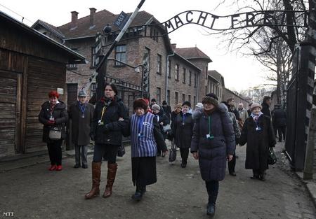"""Những cựu tù nhân sống sót qua đại nạn holocaust đi qua cổng của trại chính Auschwitz với hàng chữ khét tiếng """"Lao động giải phóng con người"""" (Arbeit macht frei) - Ảnh: Czarek Sokolowski (MTI)"""