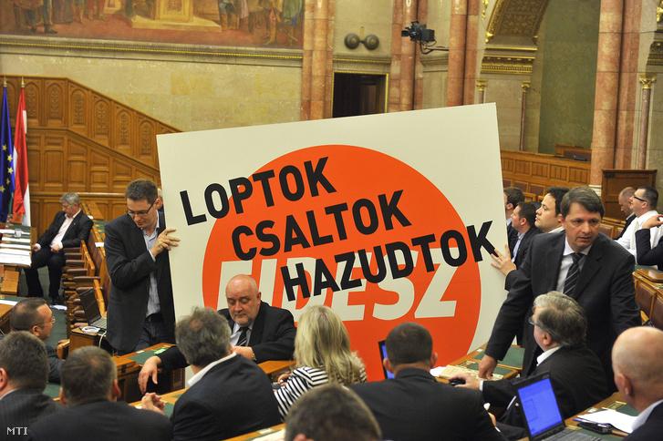 """Hai dân biểu độc lập thuộc nhóm nghị sĩ đối lập """"Đối thoại vì nước Hungary"""" (PM) giăng biển phản đối với hàng chữ """"Các người là lũ trộm cắp, lừa đảo, dối trá!"""" tại phiên họp toàn thể của Quốc hội Hungary ngày 30/4/2013 - Ảnh: Bruzák Noémi (MTI)"""
