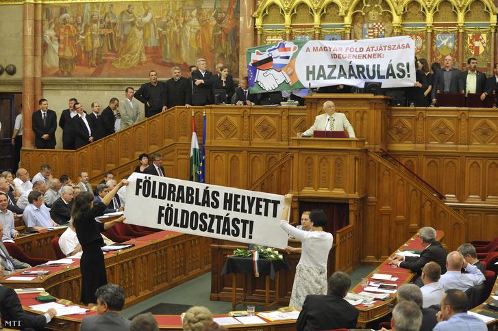 """Hai nghị sĩ độc lập thuộc đảng đối lập LMP (Chính trị có thể khác) căng một băng-rôn lớn """"Hãy chia đất thay vì cướp đất!"""". Trên bục chủ tọa là các thành viên đảng cực hữu JOBBIK với khẩu hiệu """"Để ruộng đất Hung vào tay kẻ lạ là BÁN NƯỚC!"""". phiên họp toàn thể của Quốc hội Hungary ngày 21-6-2013 - Ảnh: Soós Lajos (MTI)"""