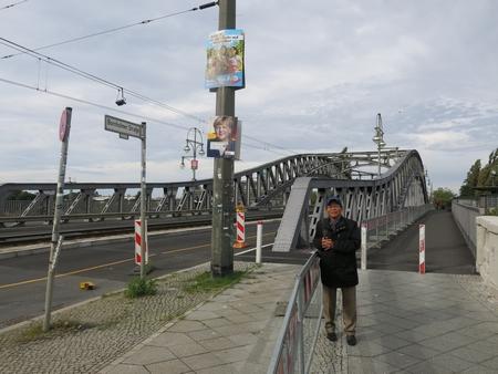 Tác giả đứng trước cây cầu Bösebrücke tại cửa khẩu Bornholmer Straße chia cắt nước Đức một thời, nơi tường thành Berlin được mở đầu tiên. Phía trên là những poster tranh cử của bà Angela Merkel, và của đảng cực hữu AfD - Ảnh tư liệu