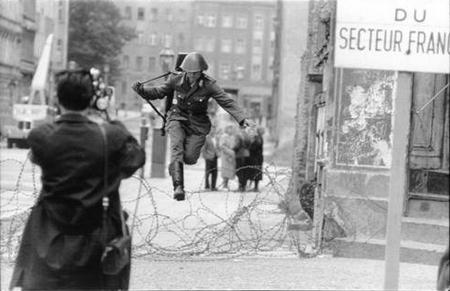"""""""Bước nhảy vào tự do"""", bức ảnh nổi tiếng của nhiếp ảnh gia Peter Leibing ghi lại khoảnh khắc người lính Đông Đức 19 tuổi Conrad Schumann vượt qua Bức tường Berlin tại phố Bernauer, khi đó đang được xây dựng và mới chỉ là một hàng rào dây thép gai"""
