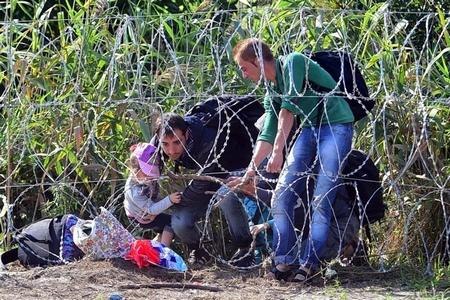Một trong những tấm ảnh có sức lan tỏa lớn của khủng hoảng tỵ nạn 2015: người tỵ nạn vuợt hàng rào ngăn biên giới Hungary - Serbia - Ảnh tư liệu