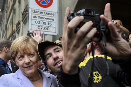 Thủ tướng Angela Merkel chụp ảnh cùng người tỵ nạn vào tháng 9-2015: quan điểm nhân đạo trong hồ sơ tỵ nạn đã khiến bà thất bại - Ảnh: Fabrice Coffrini (AFP)