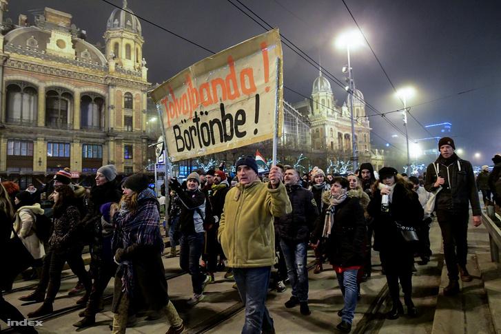 """Đoàn tuần hành đi ngang qua Ga Tây và giơ biểu ngữ kêu gọi tống cổ """"băng đảng trộm cắp"""" vào tù - Ảnh: Bődey János (index.hu)"""