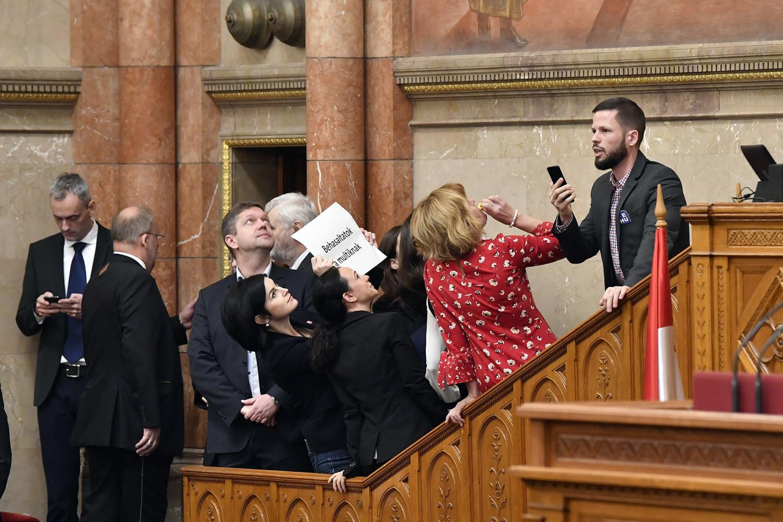 """Giới nghị sĩ đối lập chiếm bục chủ tọa và gây sóng gió chưa từng thấy trong phiên họp Quốc hội biểu quyết đạo luật """"nô lệ"""" - Ảnh: zoom.hu"""