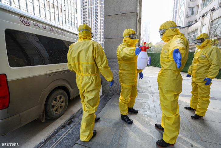 Nhân viên công ty hợp thiện khử trùng lẫn nhau sau khi đưa một tử thi vào Bệnh viện Vũ Hán ngày 30-1-2020 - Ảnh: China Daily CDIC