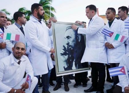 Các bác sĩ Cuba giơ cao tấm hình cố Chủ tịch Cuba Fidel Fidel trong buổi lễ chia tay trước khi lên đường để hỗ trợ với Ý tại Havana, Cuba, ngày 21-3-2020 - Ảnh: Alexandre Meneghini (Reuters)