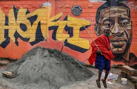 """Một ông cụ thuộc tộc Maasai ở Kenya nhảy lên bên cạnh hình George Floyd với chữ """"Haki"""" (Công bằng) - Ảnh: Brian Inganga"""