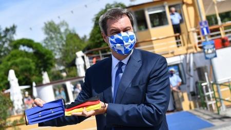 Thủ hiến bang Bayern, ông Markus Söder với hai khẩu trang mẫu quốc kỳ Đức và Liên Âu trong tay - Ảnh: Frank Hörmann (MTI/EPA)